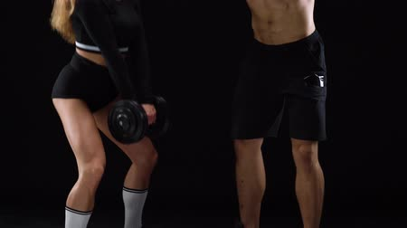 energia : Athletic man and woman crouch with extra weight, training their legs and buttocks on a black background in studio Wideo
