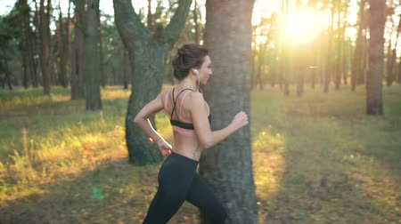 cipő : Close up of woman with headphones running through an autumn forest at sunset. Filmed at different speeds - normal and slow motion