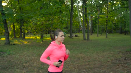 waga : Close up of woman running through an autumn park at sunset Wideo