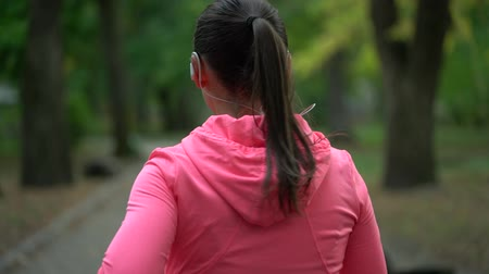 waga : Close up of woman running through an autumn park at sunset, back view. Wideo