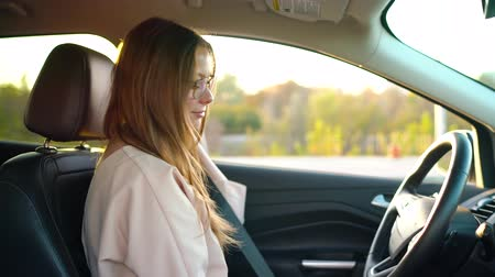 empresária : Beautiful girl with glasses inserted wireless headphones into her ears and fastened her seat belt about to drive away in a car