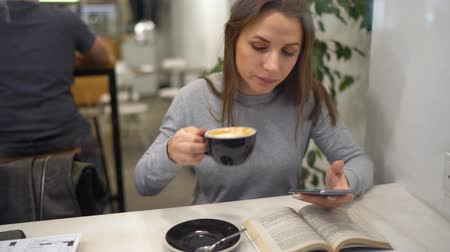 empresária : Beautiful woman spends her time in a cafe: reading a book, talking on the phone and drinking coffee