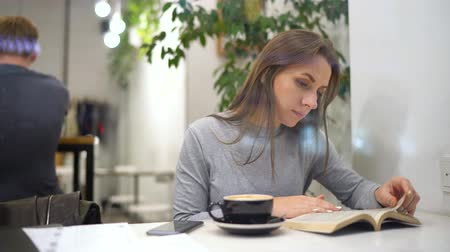 empresária : Beautiful woman spends her time in a cafe: reading a book and drinking coffee Stock Footage