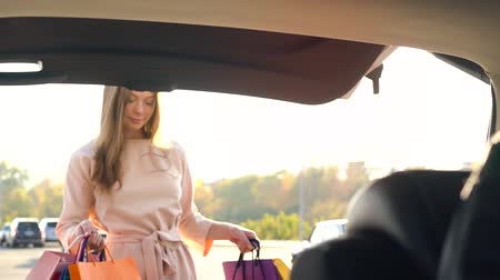 сумки : Beautiful girl puts shopping bags in the trunk of a car and leaves, intending to drive away Стоковые видеозаписи