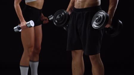 energia : Athletic man and woman flexes their hands with dumbbells, training their biceps on a black background in studio