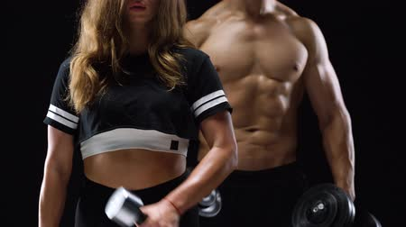 リフト : Athletic man and woman flexes their hands with dumbbells, training their biceps on a black background in studio