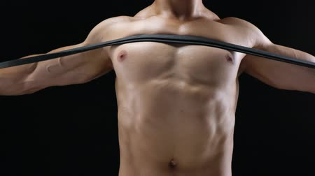 vzpírání : Athletic man doing exercise on his shoulders with elastic band on a black background in studio
