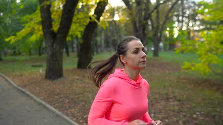 waga : Close up of woman running through an autumn park at sunset. Slow motion