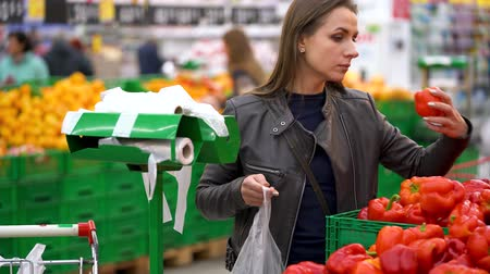 tüketici : Woman chooses red bell pepper in the supermarket