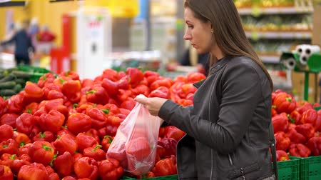 bakkaliye : Woman chooses red bell pepper in the supermarket