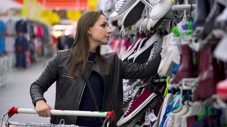 tüketici : Woman chooses sports or home shoes in the supermarket Stok Video