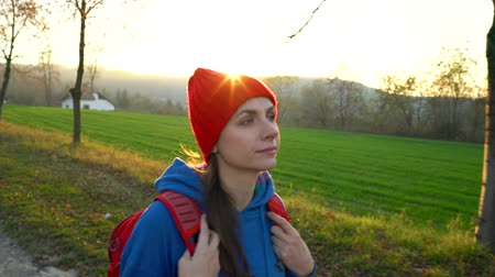 beira da estrada : Woman traveler with a backpack walks on the road in the countryside and admires the surrounding scenery Stock Footage