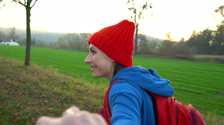 podróż : Follow me - happy young woman in red hat pulling guys hand. Hand in hand walking among the fields in the countryside