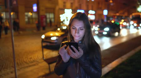 gadżet : Attractive woman uses a smartphone while walking through the streets of the evening city Wideo