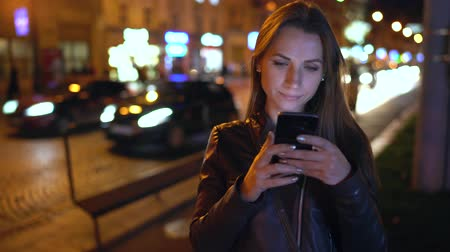 noc : Attractive woman uses a smartphone while walking through the streets of the evening city Wideo