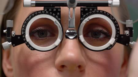 diagnóstico : Woman at the reception of an ophthalmologist. Eye examination and selection of spectacle lenses Stock Footage