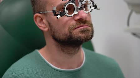 очки : Man at the reception of an ophthalmologist. Eye examination and selection of spectacle lenses