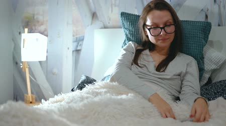 очки : Woman in glasses lies in a bed and uses a smartphone before bedtime Стоковые видеозаписи