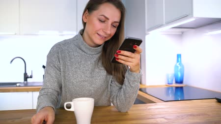 gadżet : Woman makes online payment at home with a credit card and smartphone