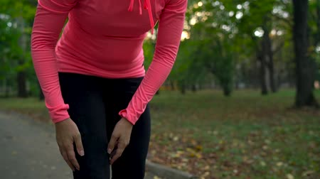 waga : Close up of woman tying shoe laces and running through an autumn park at sunset. Slow motion