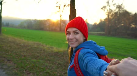 turisták : Follow me - happy young woman in red hat pulling guys hand. Hand in hand walking among the fields in the countryside