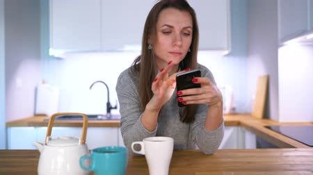 sabah : Caucasian woman having breakfast in the kitchen and using a smartphone Stok Video