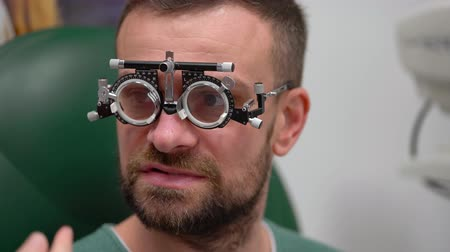 pacjent : Man at the reception of an ophthalmologist. Eye examination and selection of spectacle lenses