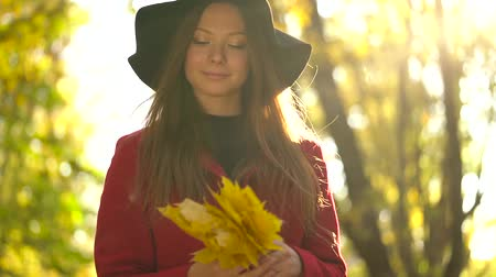 buquê : Beautiful girl in black hat walks in the autumn forest and enjoys good weather. Slow motion Vídeos