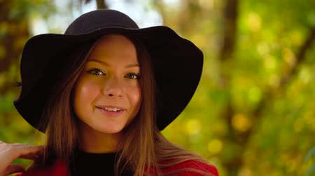 ruhák : Portrait of a beautiful smiling girl in a black hat with a yellow maple leaf in the foreground in the autumn forest