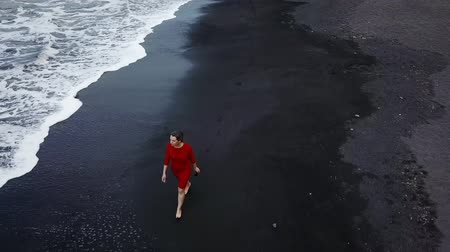 sziget : Aerial view of a girl in a red dress walking on the beach with black sand. Tenerife, Canary Islands, Spain Stock mozgókép