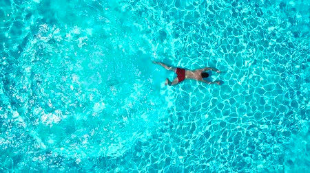 spat : View from the top as a man dives into the pool and swims under the water Stockvideo