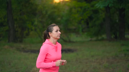 kardio : Close up of woman running through an autumn park at sunset. Slow motion