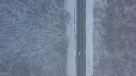 air vehicle : Aerial view of traffic on the road passing through the winter forest in severe weather Stock Footage