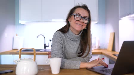 kuchnia : Caucasian woman having breakfast in the kitchen and using a laptop