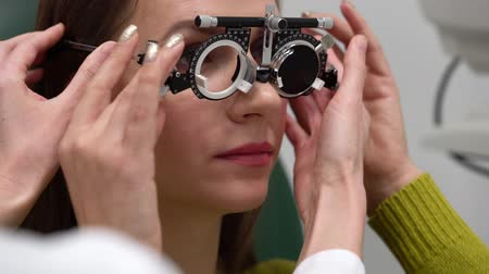 очки : Woman at the reception of an ophthalmologist. Eye examination and selection of spectacle lenses Стоковые видеозаписи
