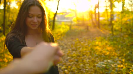 ruhák : Beautiful girl holds the hand of her boyfriend and follows him through the yellow autumn forest. Slow motion