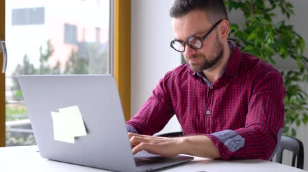 dialog : Beared man in glasses sitting at home office and working on a laptop