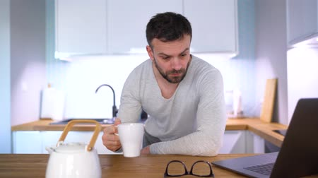 kuchnia : Bearded sleepy man having breakfast in the kitchen and using a laptop