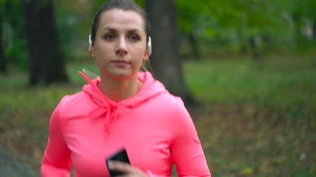 kardio : Close up of woman chooses music and running through an autumn park at sunset. Dostupné videozáznamy