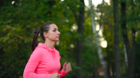 waga : Close up of woman running through an autumn park at sunset. Wideo