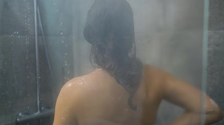 szampon : Woman washes her hair, shoulders, arms and back in the shower. Hair care, beauty and wellbeing concept.