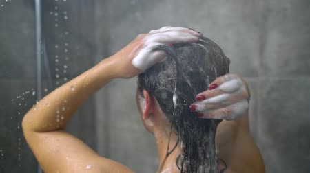 szampon : Woman washing her hair with shampoo. Hair care, beauty and wellbeing concept. Slow motion