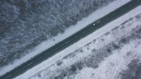sníh : Aerial view of traffic on the road passing through the winter forest in severe weather Dostupné videozáznamy