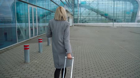 nástup do letadla : Blonde girl rolls a suitcase near the airport terminal - view from the back. Slow motion Dostupné videozáznamy
