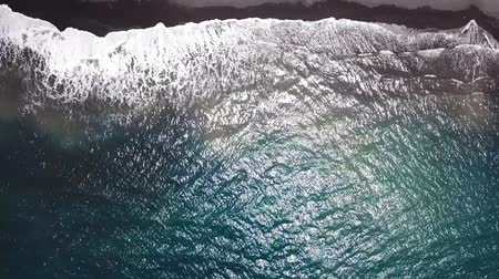 kanári : Top view of a deserted black volcanic beach. Coast of the island of Tenerife. Aerial drone footage of sea waves reaching shore Stock mozgókép