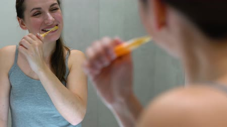 совершенство : Pretty woman brushing her teeth in a bathroom in the morning. Morning hygiene. Стоковые видеозаписи