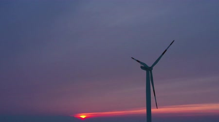 elétrico : Silhouette of energy producing wind turbines at sunset, Poland. Filmed at various speeds: normal and accelerated Stock Footage