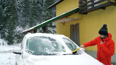 щеткой : Man cleans the car from the snow near his house