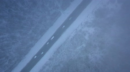 air vehicle : Aerial view of traffic on the road passing through the winter forest in blizzard Stock Footage