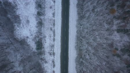 air vehicle : Aerial view of empty road passing through the winter forest in blizzard